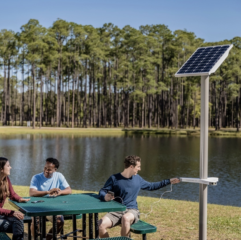 Image of a man sitting at a picnic table using a Solar Charging Kit to charge his device