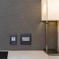Black wall plates and white outlets next to lamp