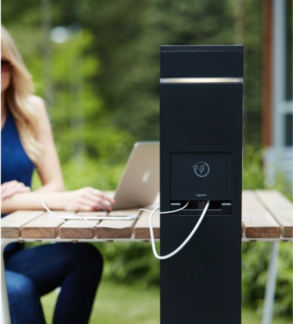 Person using laptop with outdoor charging station installed near outdoor table