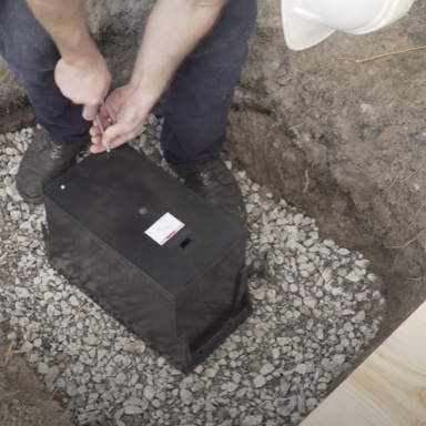 man installing outdoor ground box in ground