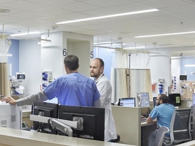 Doctor and nurse speaking at nursing station inside hospital
