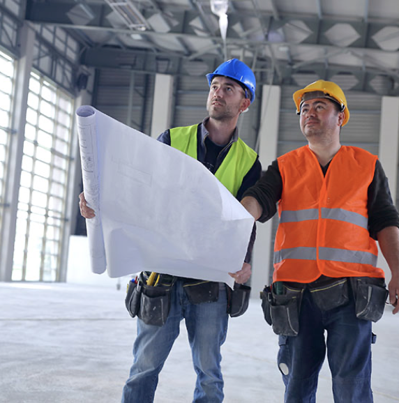 Construction workers looking at blue prints with hard hats on