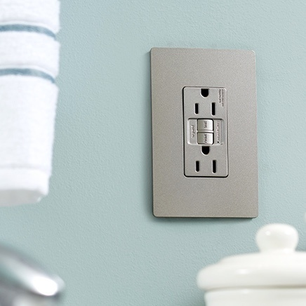 Grey radiant GFCI outlet installed in blue bathroom wall