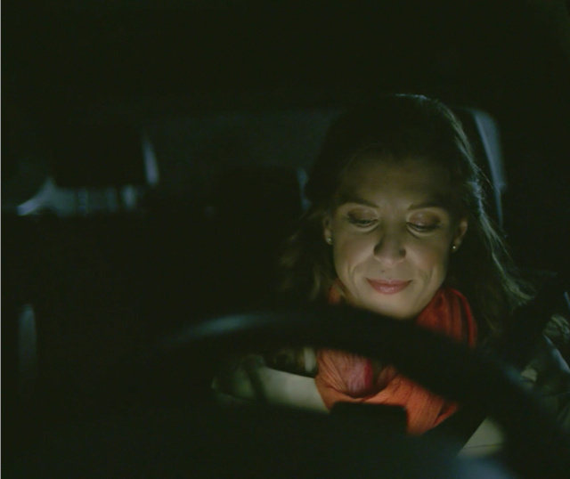 woman sitting in car driver's seat at night checking phone