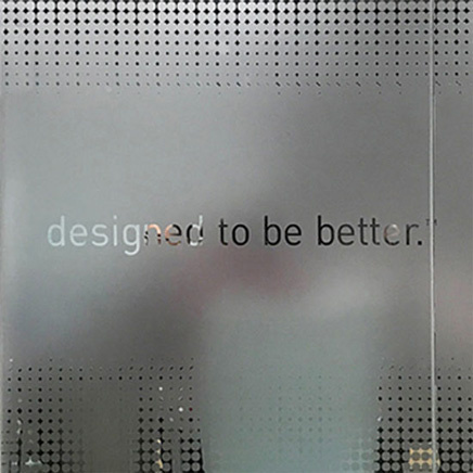 "Translucent glass wall with the words ""designed to be better"" engraved on it"