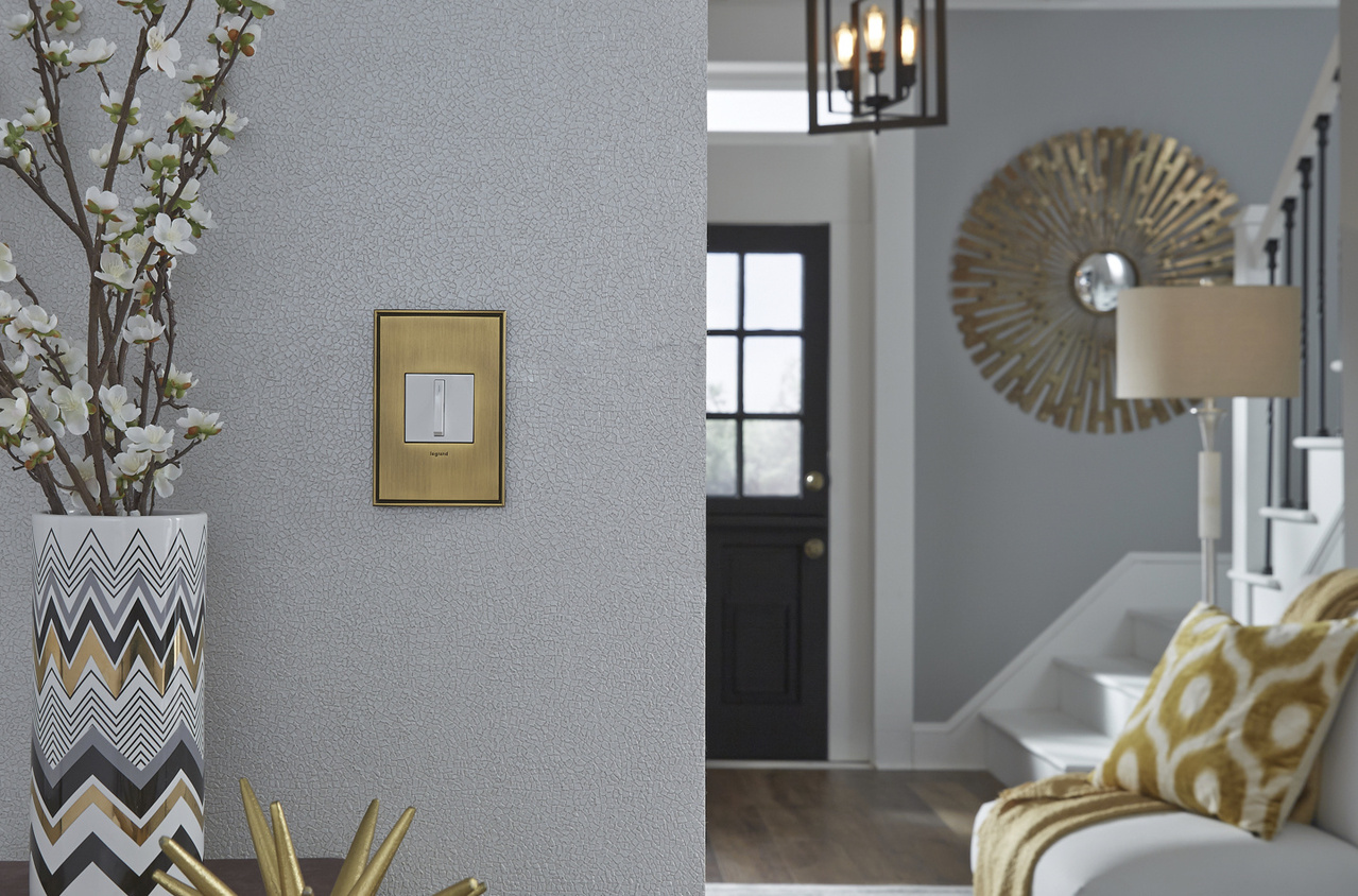 adorne Collection by Legrand light switch with Brushed Satin Brass designer wall plate on gray living room wall