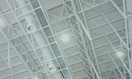 vaulted ceiling with white steel rafters and bright lighting
