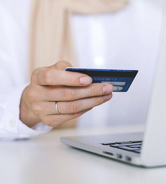 Woman entering credit card information online while she is on her laptop