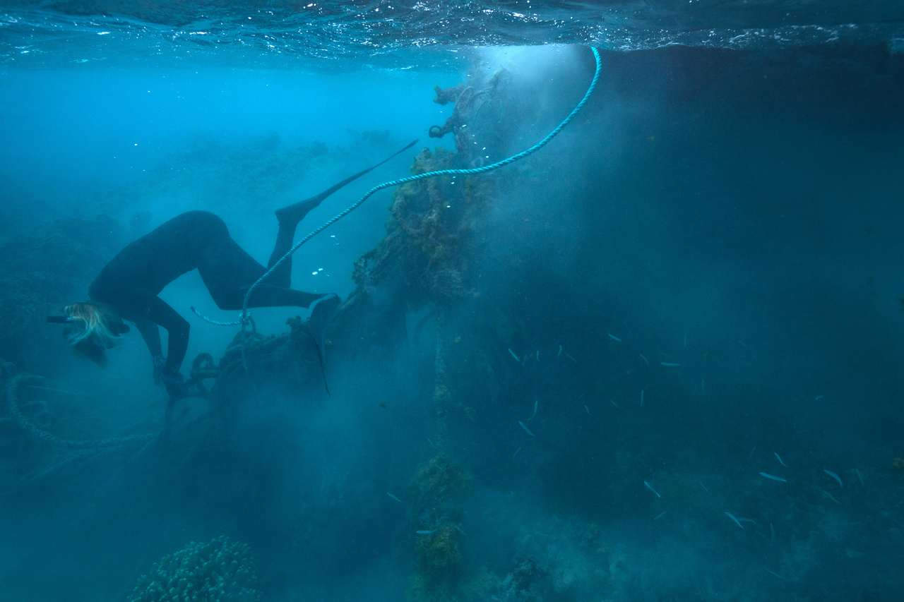 Marine debris diver clears derelict fishing net from the reef at Pearl and Hermes Atoll