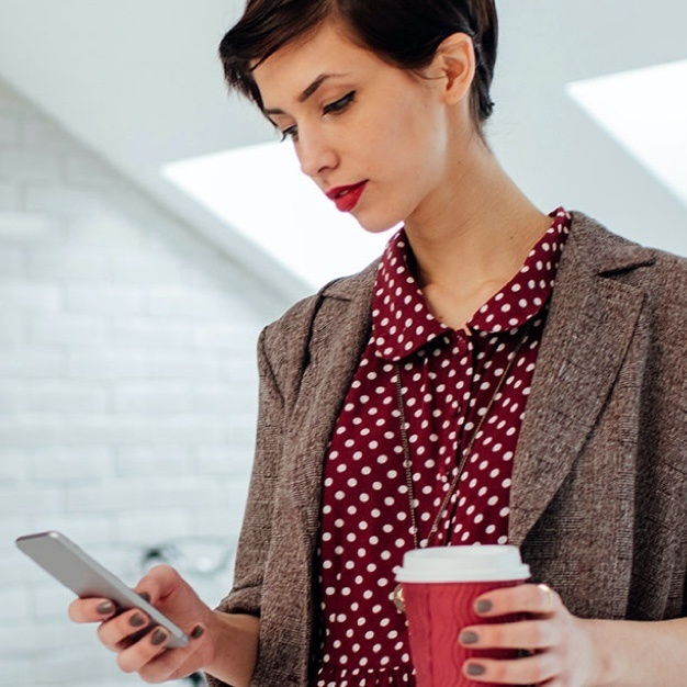 Woman looking at phone with red poka dot shirt and coffee in hand