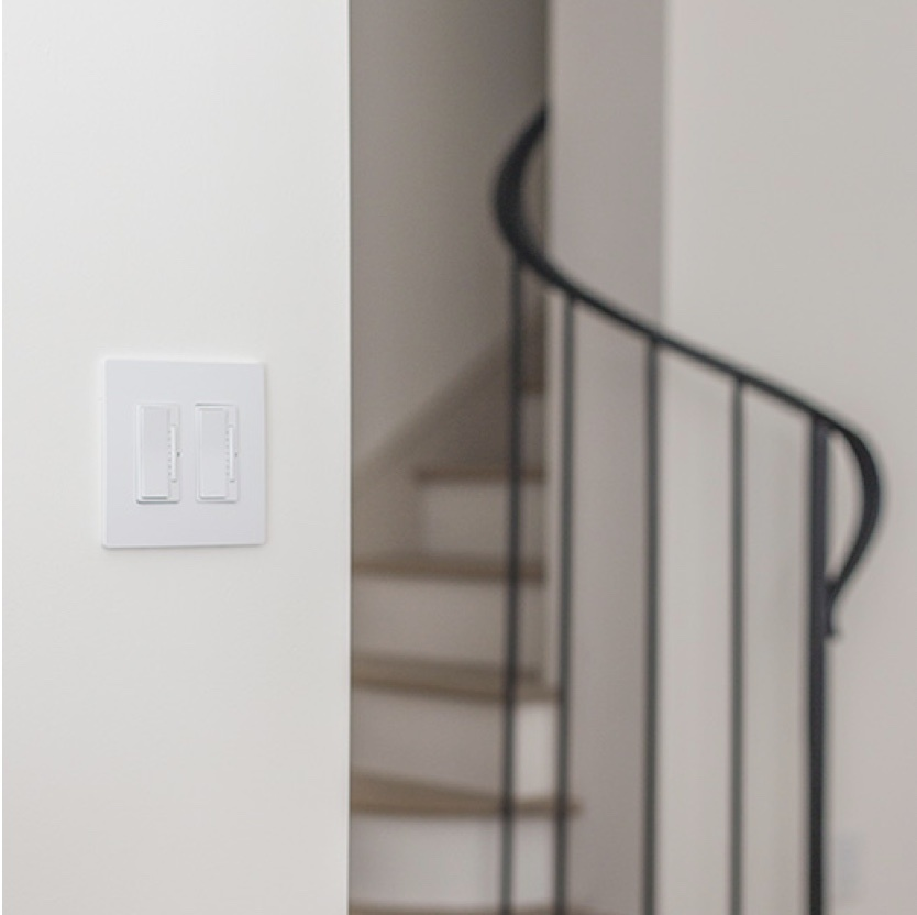 white light switch on white wall next to iron spiral staircase