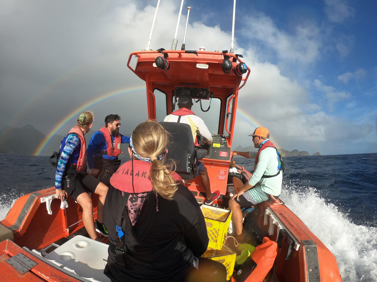 Scientists hang on as the small boat Metal Shark transits into rougher weather on the way to one of their permanent sites. We experience many conditions out here, including rain showers and rainbows! (Photo: NOAA Fisheries/Evan Barba)