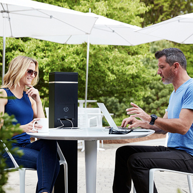 Couple working at outdoor table using outdoor charging station