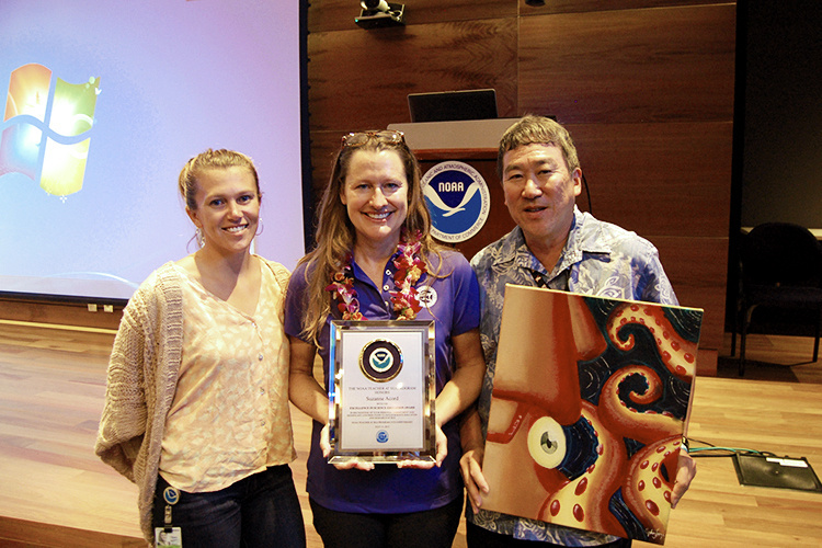Teacher at Sea getting awarded by two scientists.