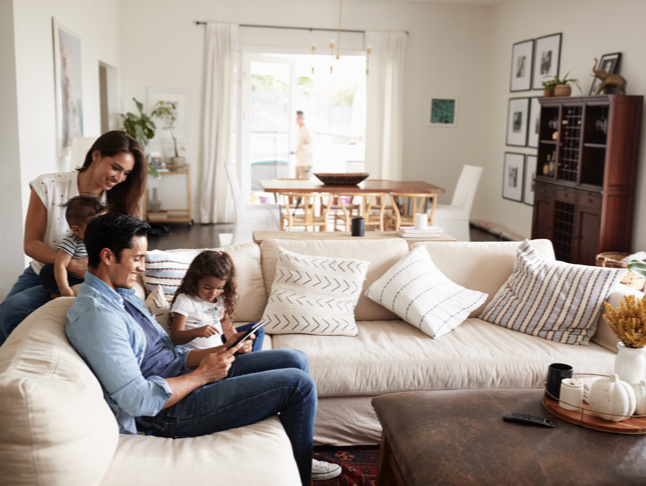 family sitting on beige couch in white room looking at smart devices