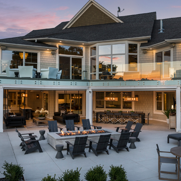 Exterior of home with one outdoor seating area on the second level and the second area with adirondack chairs and a firepit
