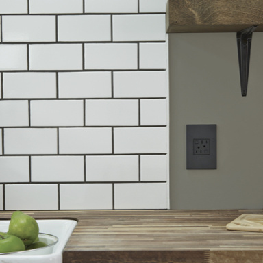 Black outlet on gray wall next to white subway tile