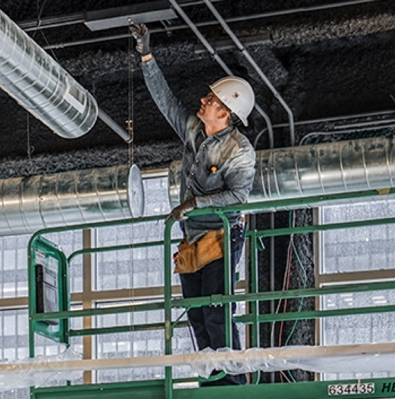 Building inspector on a step ladder looking at the ceiling in an industrial building