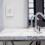 White marble sink with white outlet on nearby wall