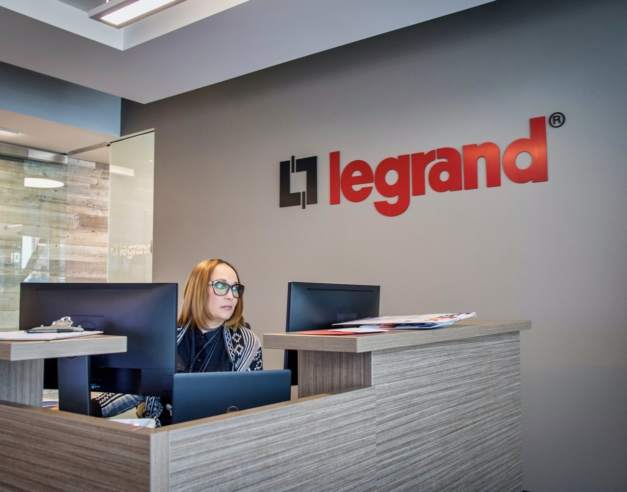 Woman sitting at a desk looking at her computer in front of a gray wall with the Legrand logo printed on it