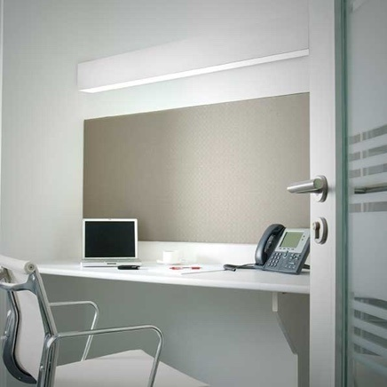 Office space with wall lighting, laptop, and work phone