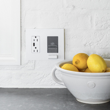 White radiant wireless charger next to white bowl of lemons