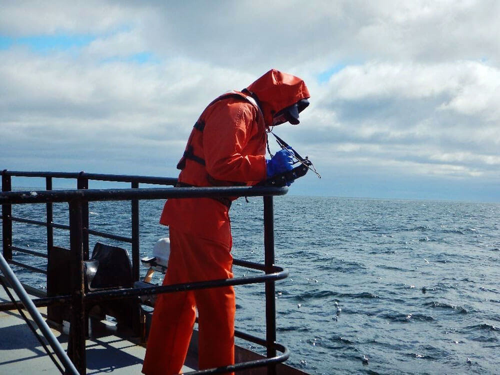 Man aboard fishing vessel looking out at sea