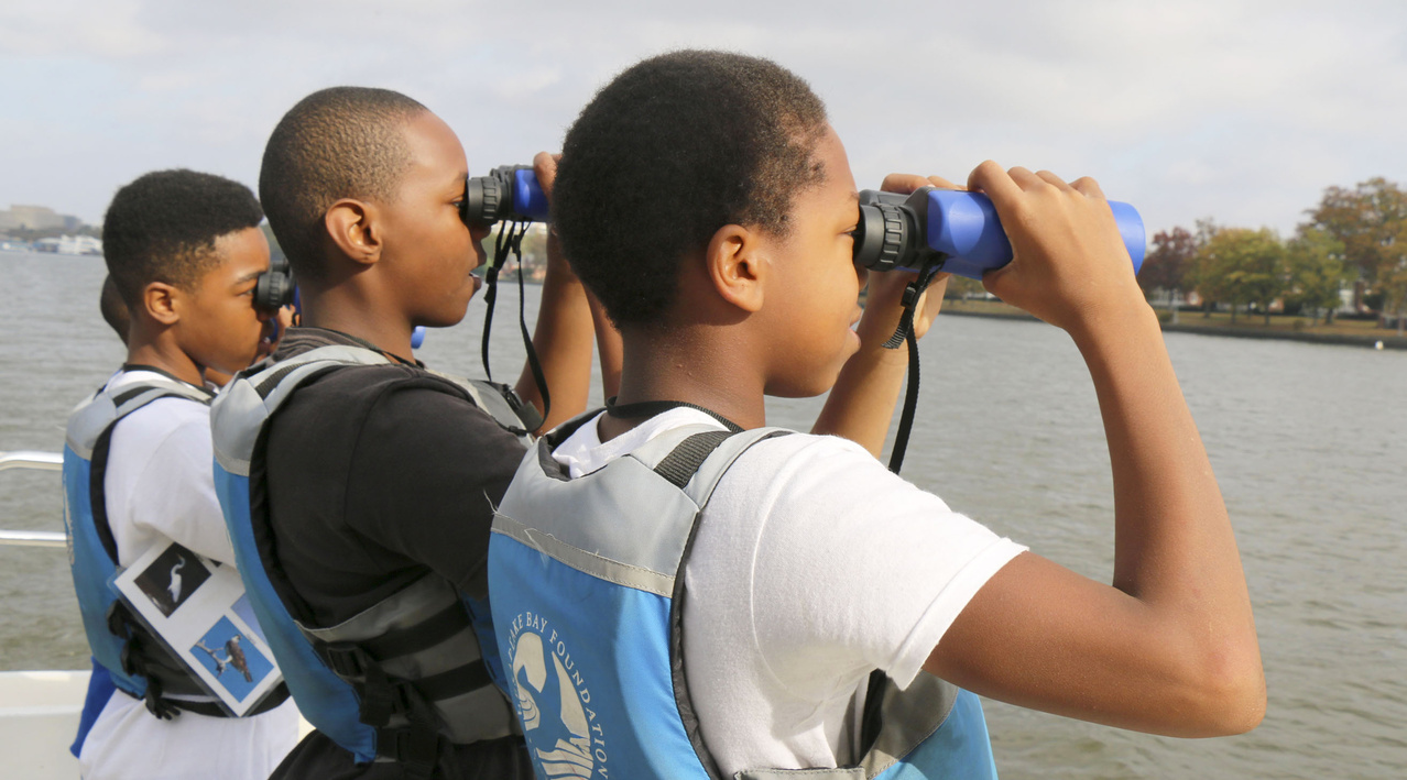 Students view the water through binoculars.