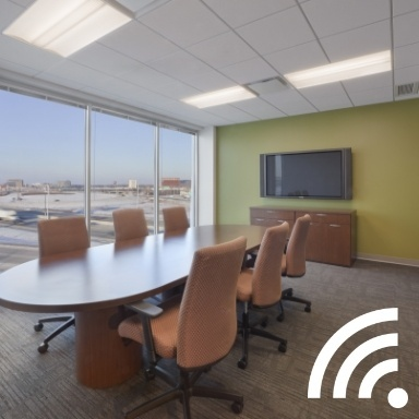 Long oval conference table with 6 beige rolling chairs around it in front of a green wall with a mounted flat screen tv and table adjacent