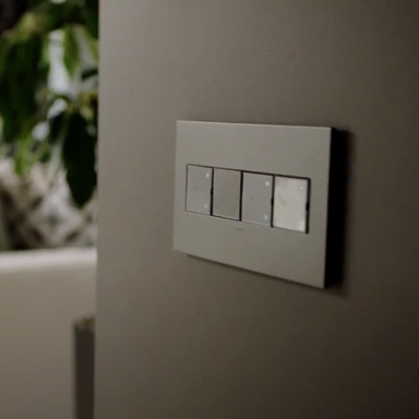 Gray light switches and dimmers on brown wall to entryway