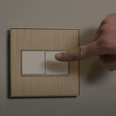 Finger turning on white light switch with wooden wall plate
