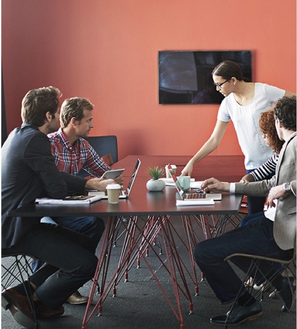 Five people sitting or standing around conference table with red wall and TV display screen