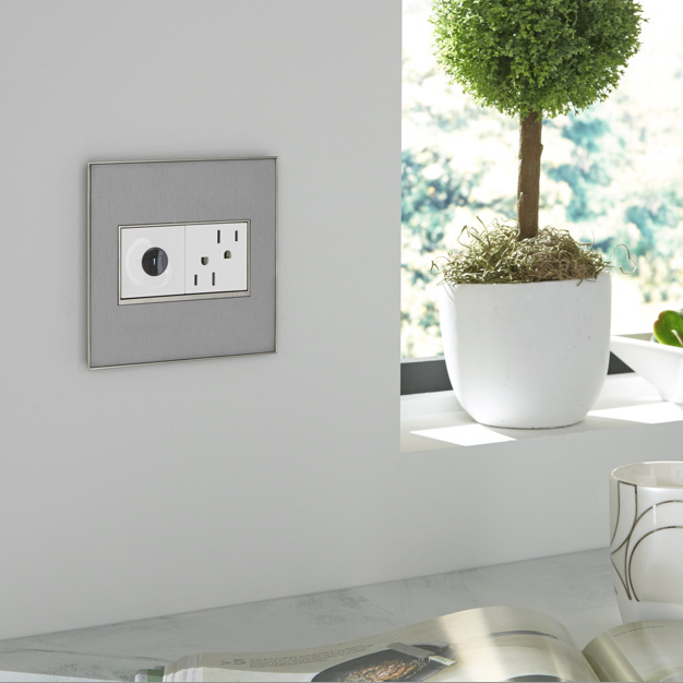 White adorne wave switch and outlet with silver wall plate in kitchen