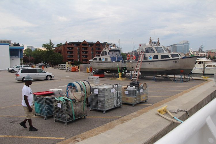 Pallets and boxes of gear sit on dock awaiting loading onto a ship
