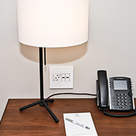 Hotel desk with phone, lamp, and white outlets
