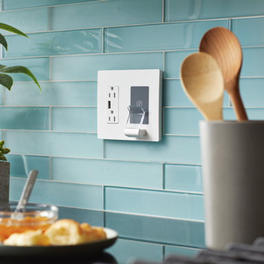 White wireless charger in kitchen with teal tile and wooden spoons