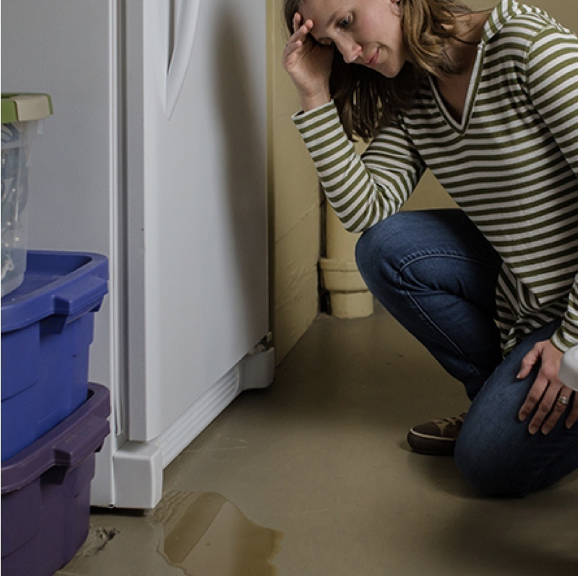 woman looking at water leak on hard wood flooring