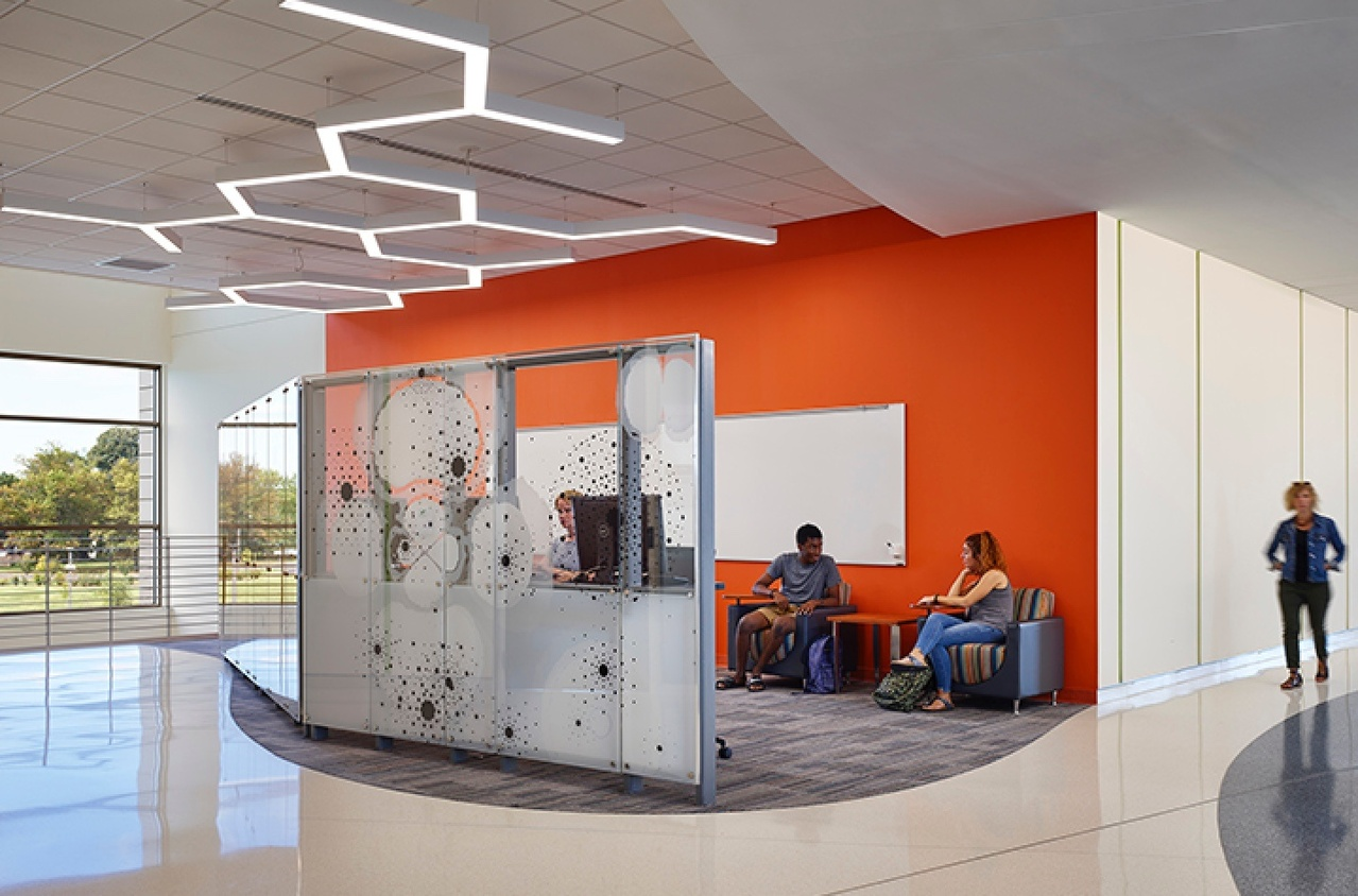 Orange wall and students hanging out in an open space