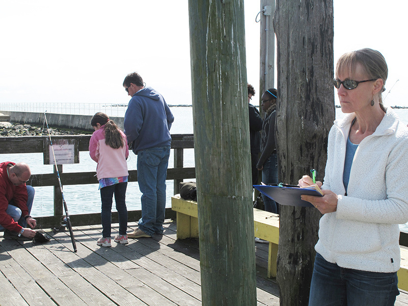 Lisa Colburn taking notes on dock