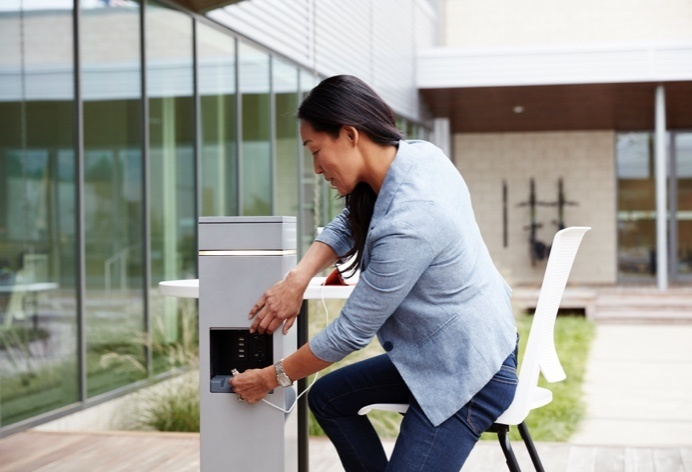 Person using outdoor charging station installed in courtyard space