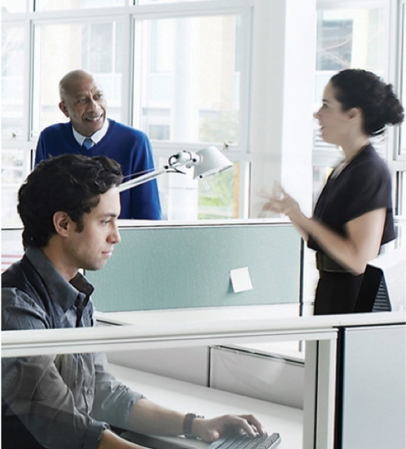 Three office workers chatting in modern office cubicle