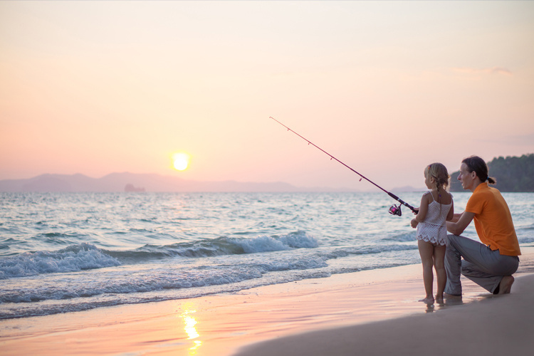 A parent and child fish on a beach at sunset.