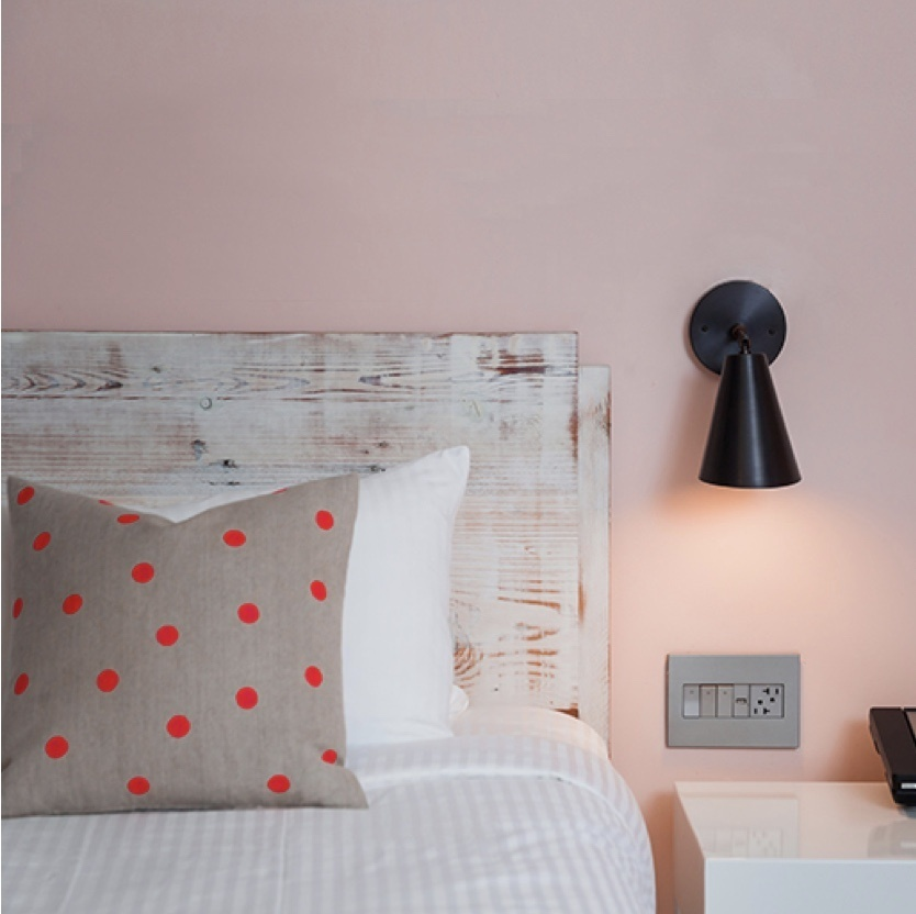 Hotel bed with adorne furniture power center in wall above nightstand