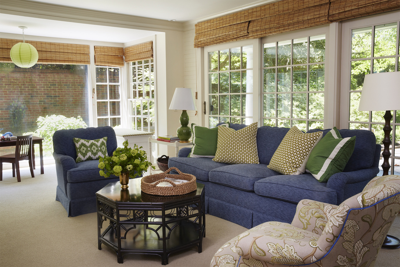 """""""This family room is where everyone hangs out to watchTV,"""" says the designer, """"So it needed to becomfortableanddurable. I lovenavy blue upholstery as a durable alternative to beige and grey. TheseCharles Stewart sofas are upholstered in Duralee fabric with Schumacherthrow pillows."""""""