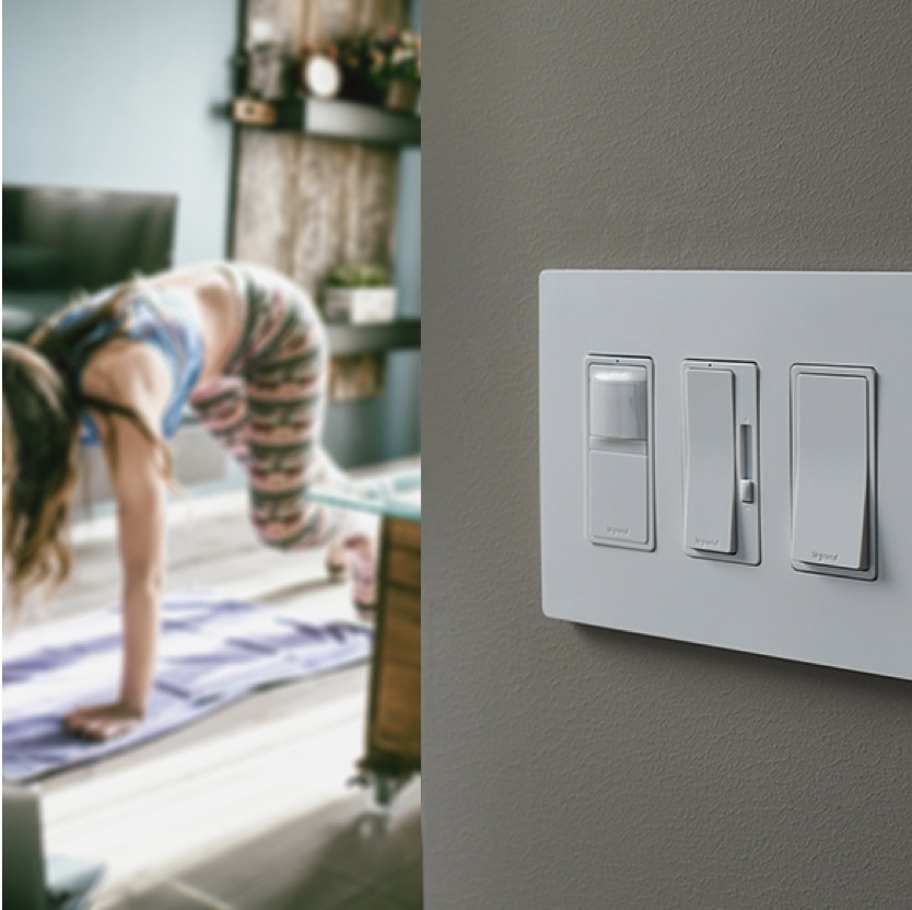 Woman doing yoga in background with light switches on wall
