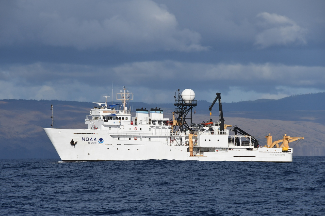 Large white research ship against blue ocean