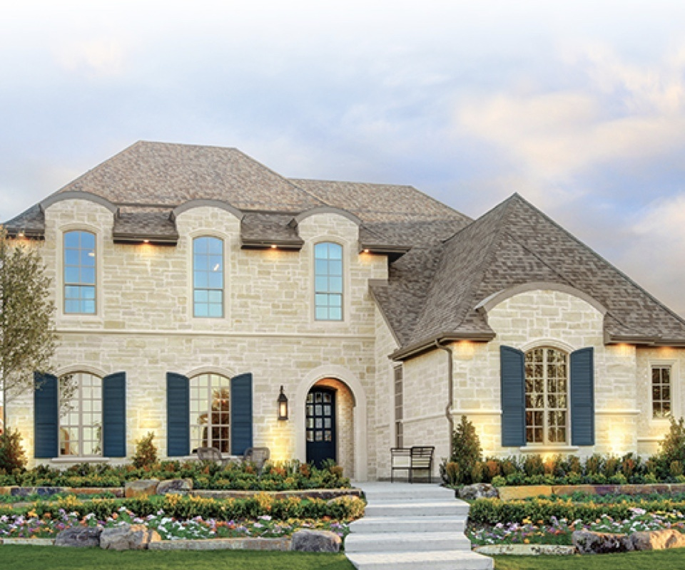 exterior of two-floor stone home with dark green shutters and large front yard