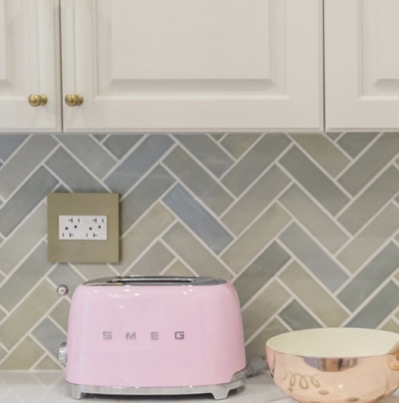 Brass wall plate and white outlets against green chevron kitchen backsplash with pink toast on kitchen counter