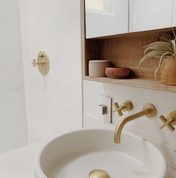 white bathroom sink with brass accents