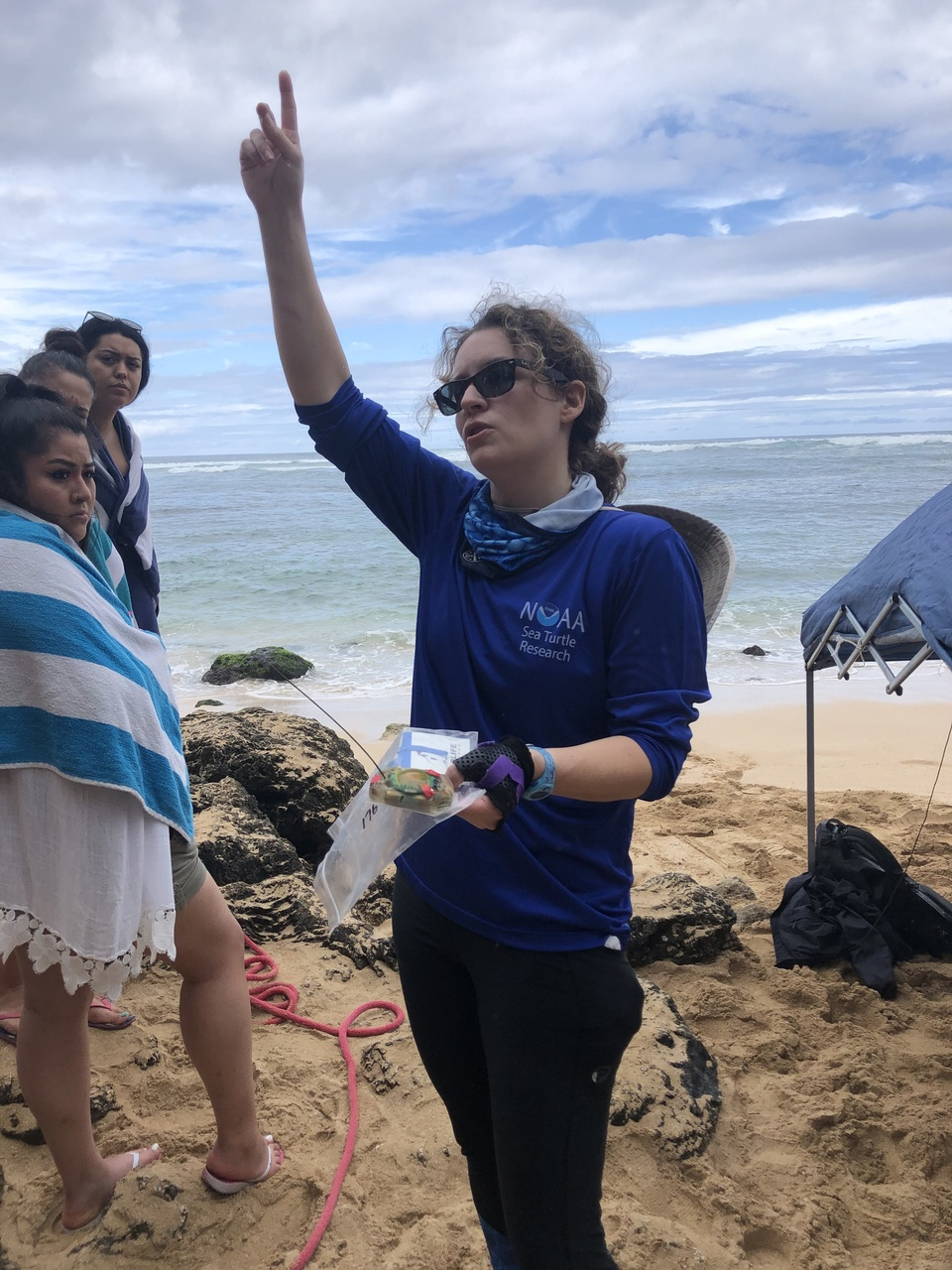 Scientist raising hand in air and speaking on the beach.